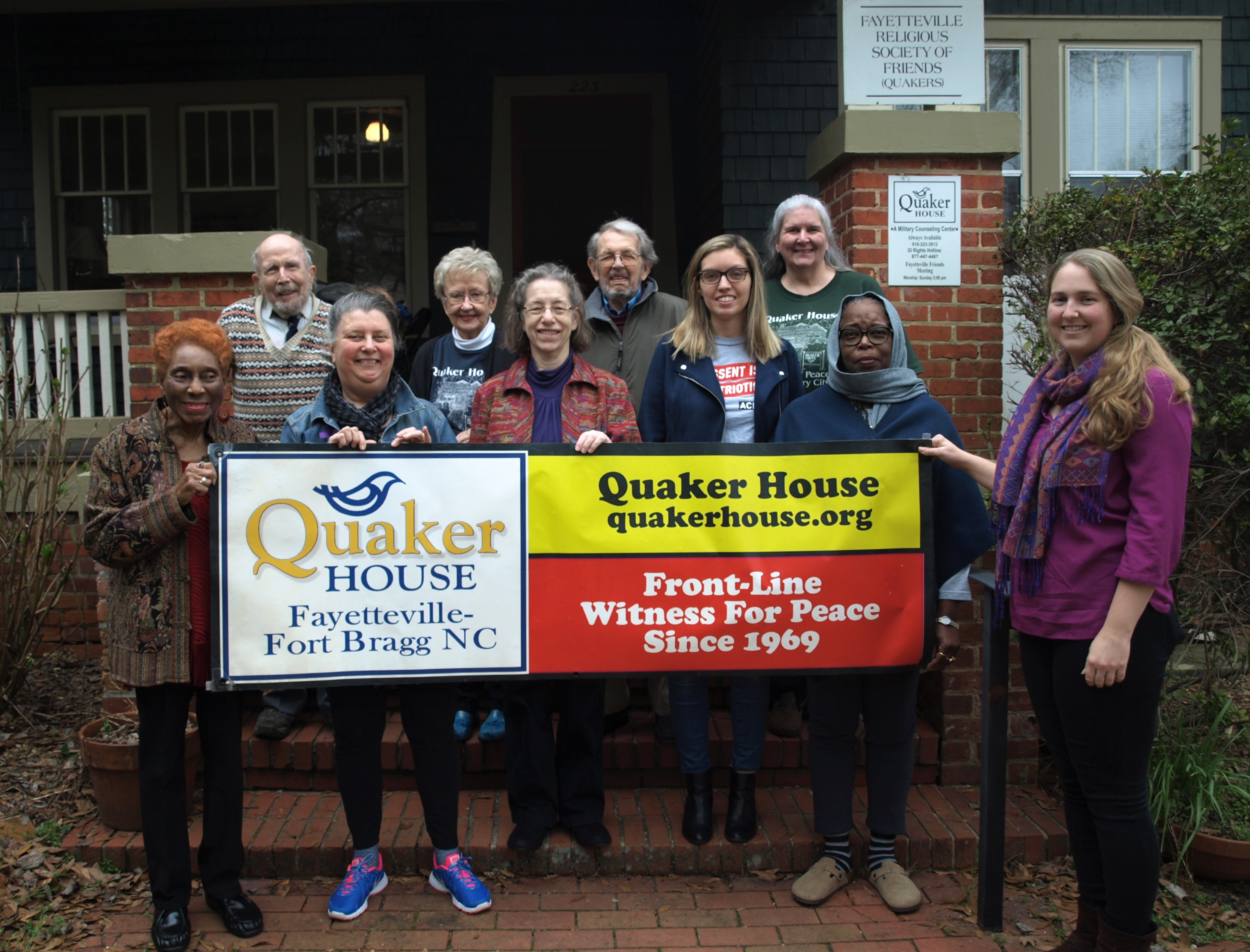group of people holding Quaker House sign in front of House