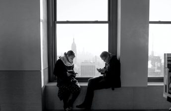 Two people reading while sitting in a windows. Black and white photo.
