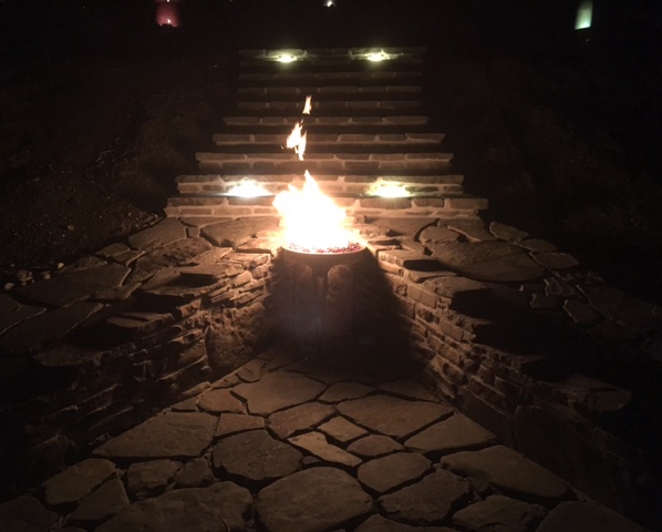 custom stone fire pit lit at night