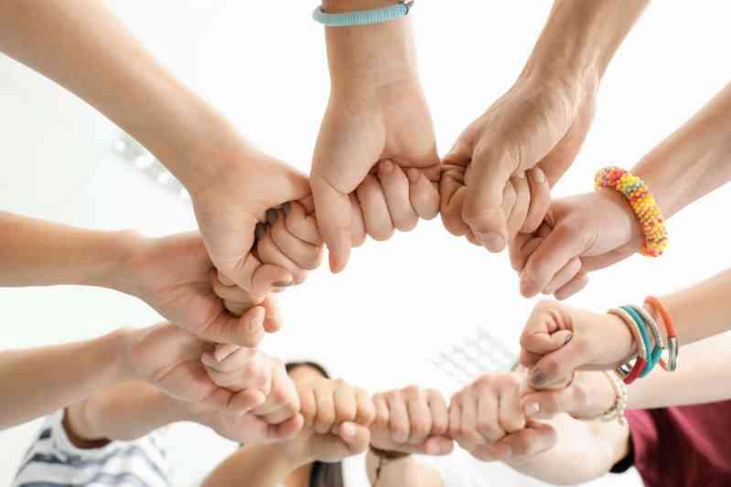 Groupe de personnes assemblant leurs poings en signe d'unité