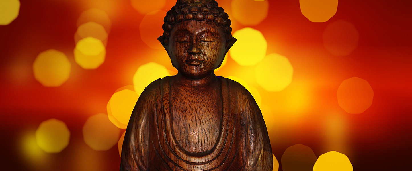 Buddha statuette and bokeh lights