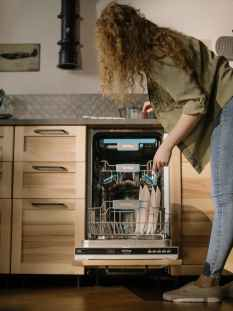 woman in gray jacket and blue denim jeans standing in front of dishwasher