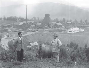 Joseph Divis and a companion overlooking the headworks for the Blackwater mine at Waiuta. The prominent mullock (waste) heap in the centre had been levelled to provide a bowling green.