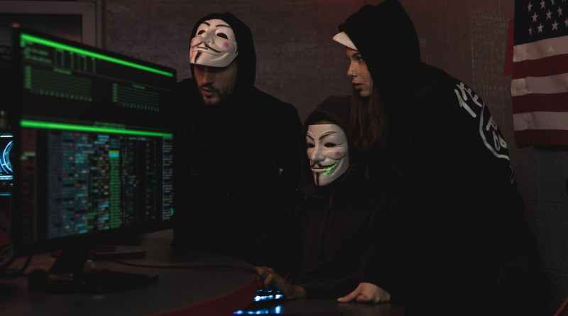 three people hacking a computer system