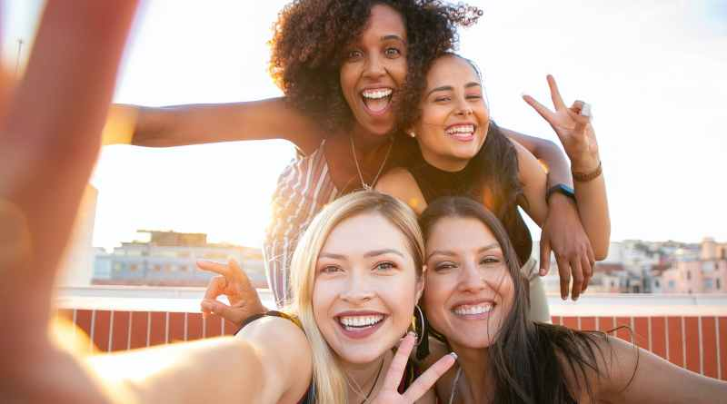 cheerful young diverse women showing v sign while taking selfie on rooftop
