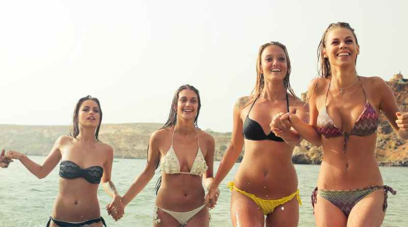 group of women wearing bikini on body of water
