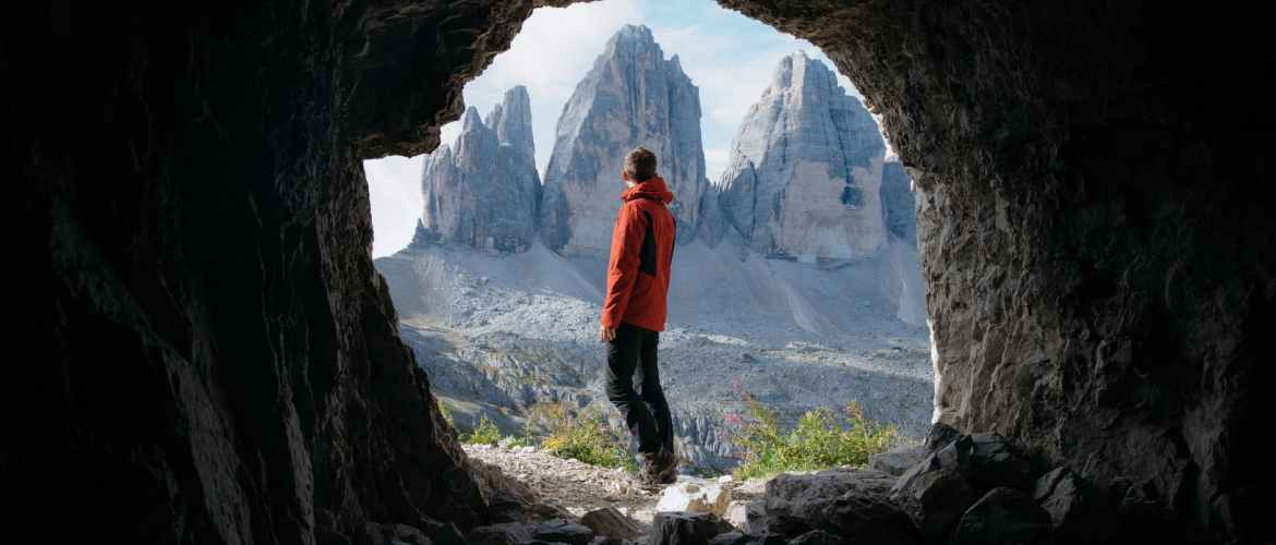 man in red jacket standing outside of the cave across the three mountains