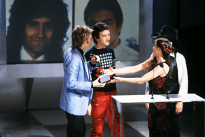 roger-taylor-and-john-deacon-receiving-the-award-for-favourite-pop-single-for-another-one-bites-the-dust-from-barbi-benton-and-johnny-paycheck-american-music-awards-january-1981