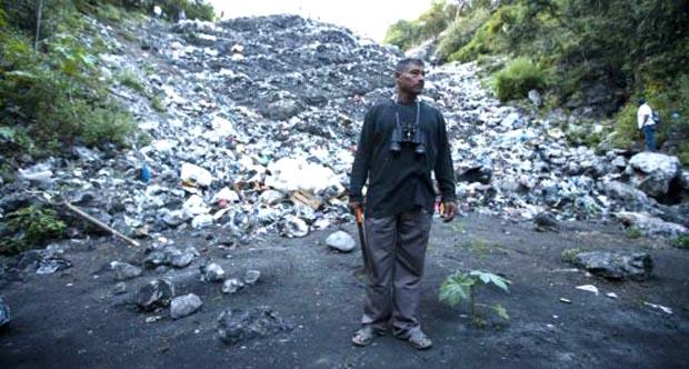 En el basurero de Cocula, un padre trata de hallar alguna prueba que explique la forma como mataron y quemaron a los normalistas. Foto Saul Ruiz