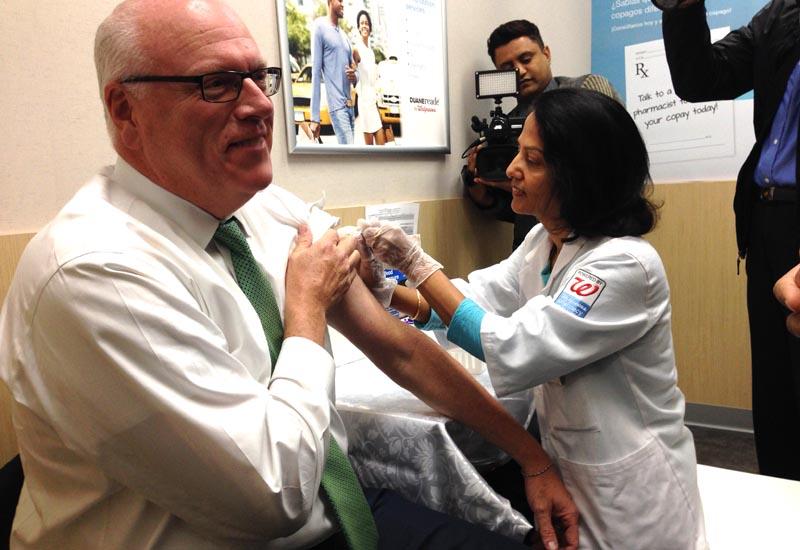 El congresista Crowley aplicándose la inyección contra la gripe en la farmacia Walgreens.