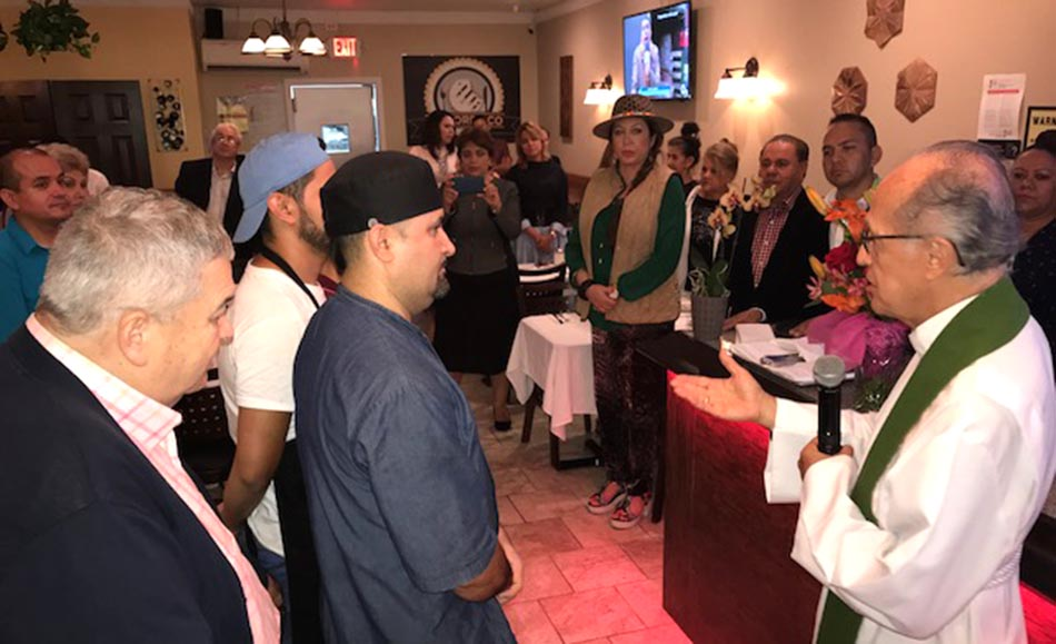 El reverendo Mario Martínez bendiciendo el restaurante El Mordisco, frente a empleados, invitados y el activista Orlando Tobón.