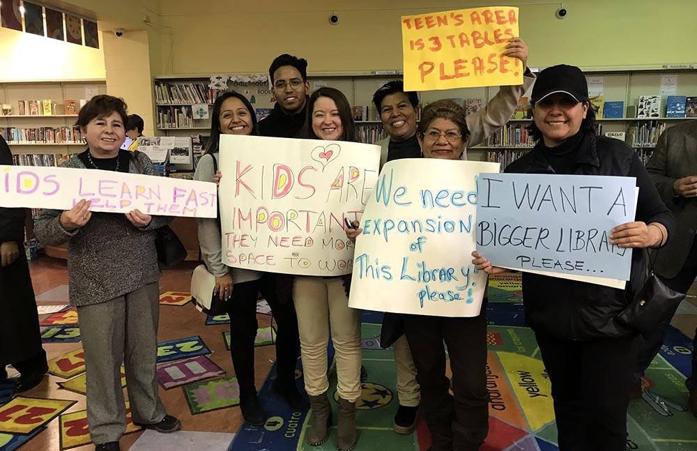 Activistas de la comunidad latina exhibieron carteles en busca de la expansión de la biblioteca pública de Corona, Queens.