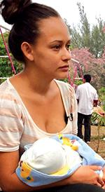 Madre hondureña cargando a su recién nacido rumbo a la frontera.