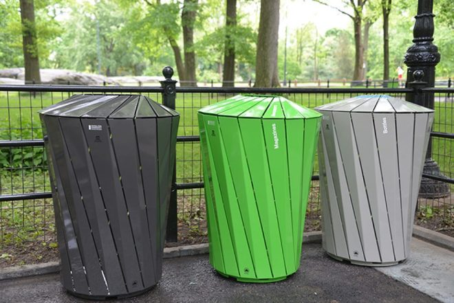 Trash cans for paper, plastics, and regular trash in a park.