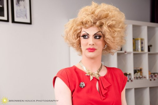 "Drag superstar Robbie Turner returns to Capitol Hill as ""Dottie Pearl the Queen Bee of TV News""."