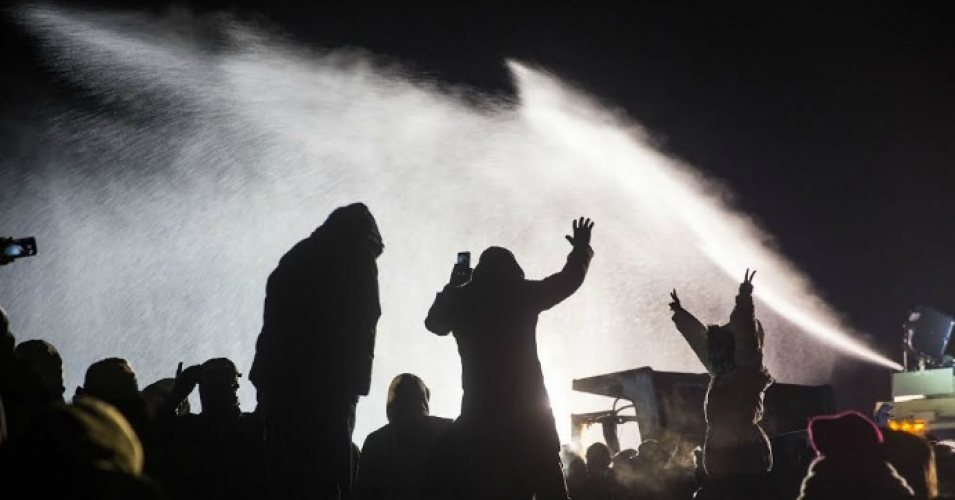 Law enforcement officers spray protesters with water cannons in below-freezing temperatures. (Photo: Tara Houska/Twitter)