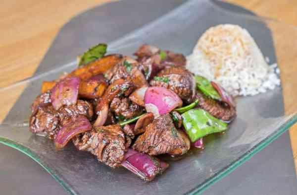 Lomo saltado, solomillo de vacuno, con cebolla morada, tomate, patatas fritas y tirabeque, acompañado de arroz