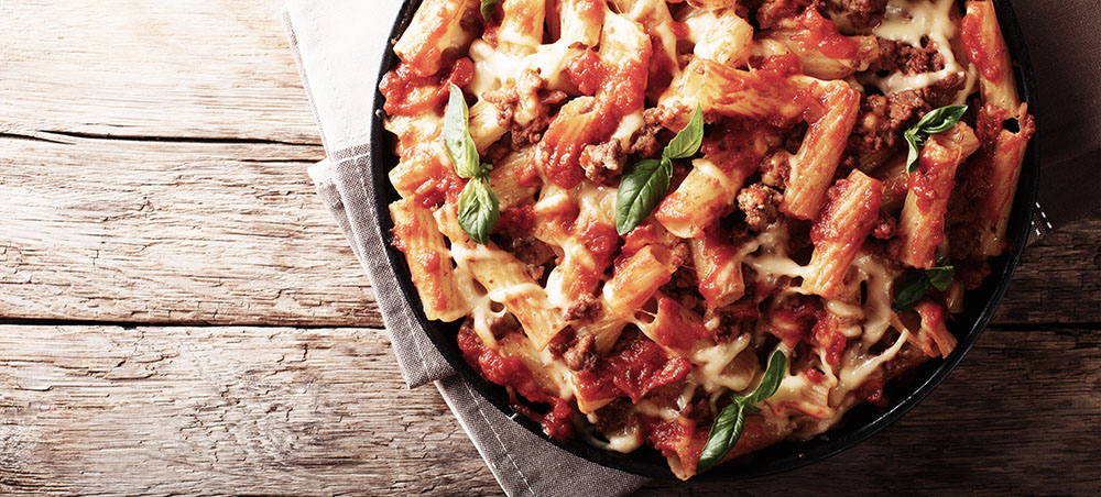 Pasta ziti with bolognese sauce and cheese close-up. horizontal top view, rustic style