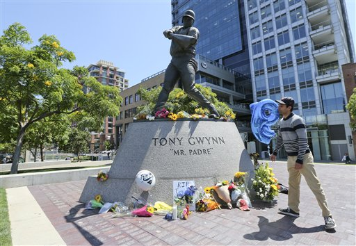 "A mourner looks up at the Tony Gwynn ""Mr. Padre"" statue outside Petco Park Monday, June 16, 2014, in San Diego. Gwynn, an eight time National League batting champion and a member of Baseball Hall of Fame, died Monday from cancer. (AP Photo/Lenny Ignelzi)"