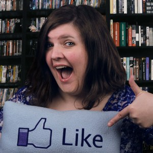 Girl holding a pillow with the Facebook like symbol