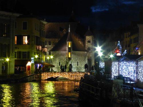Vista nocturna del Palacio de la Isla de Annecy rodeado por el Mercado de Navidad