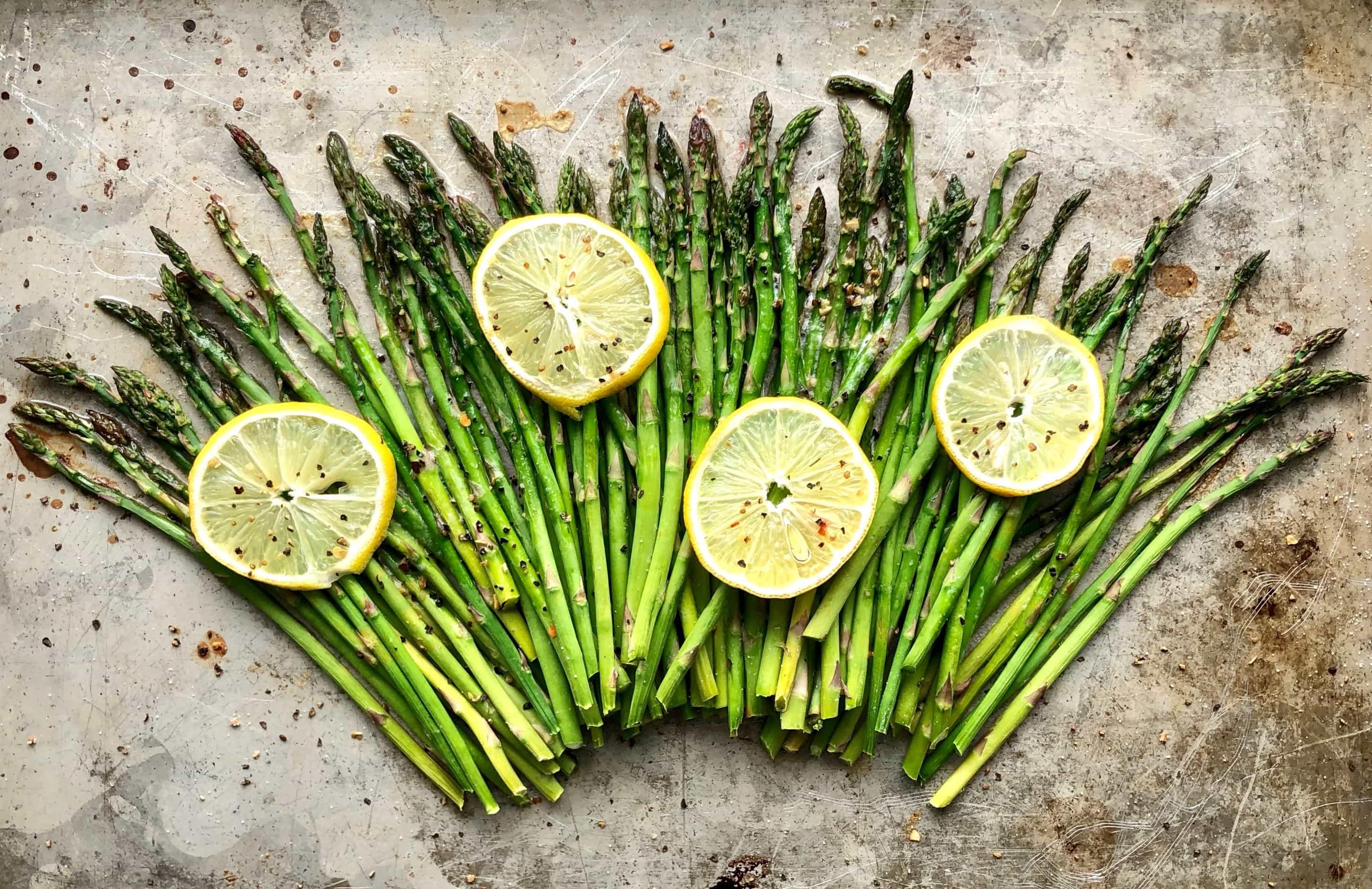 lemon butter asparagus on a pan with lemons on top