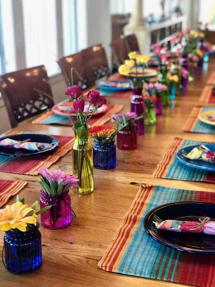 fiesta plates and colorful flowers on a long table with chairs