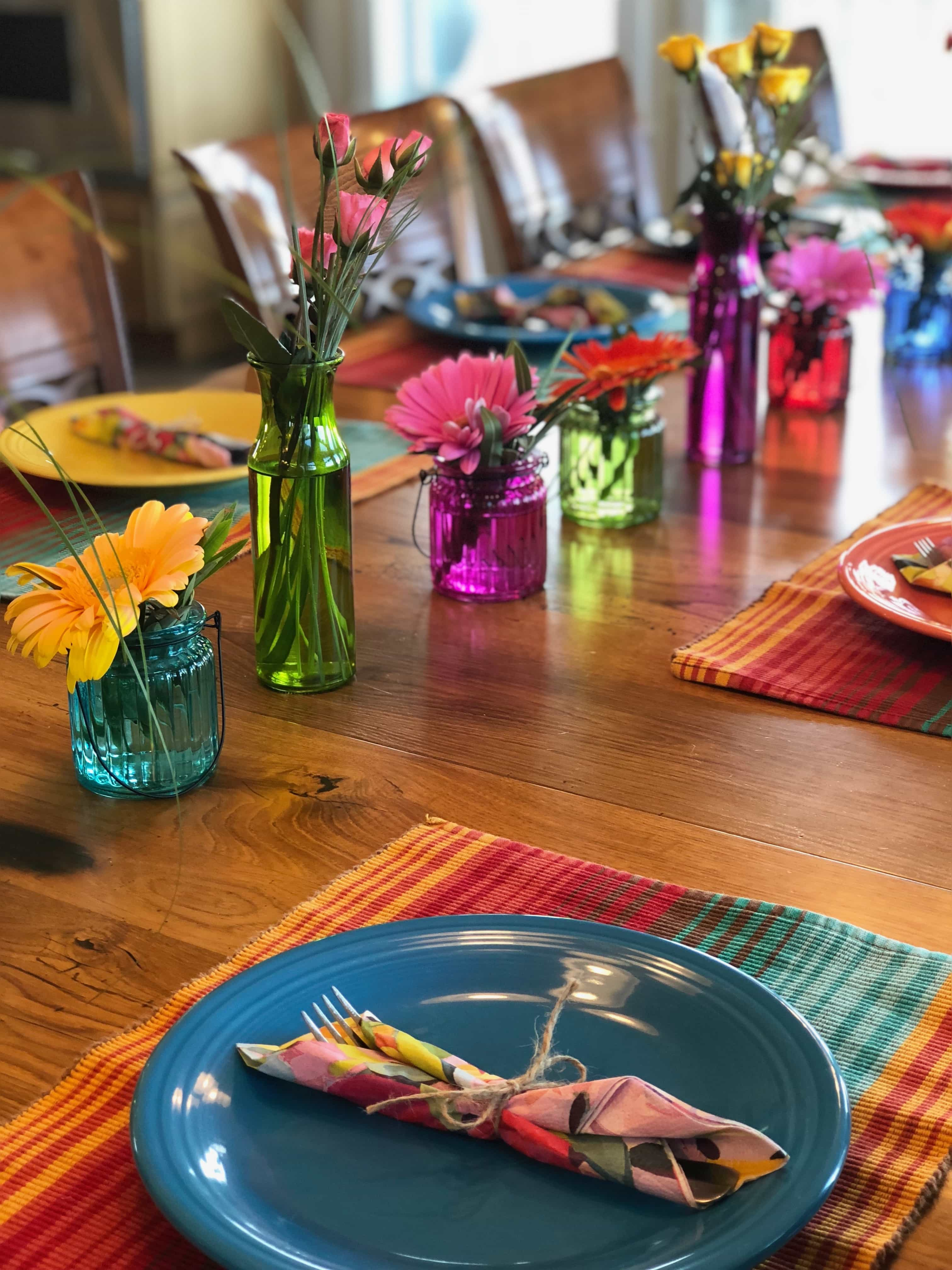 colorful and bright table decor with placemats, plates and flowers
