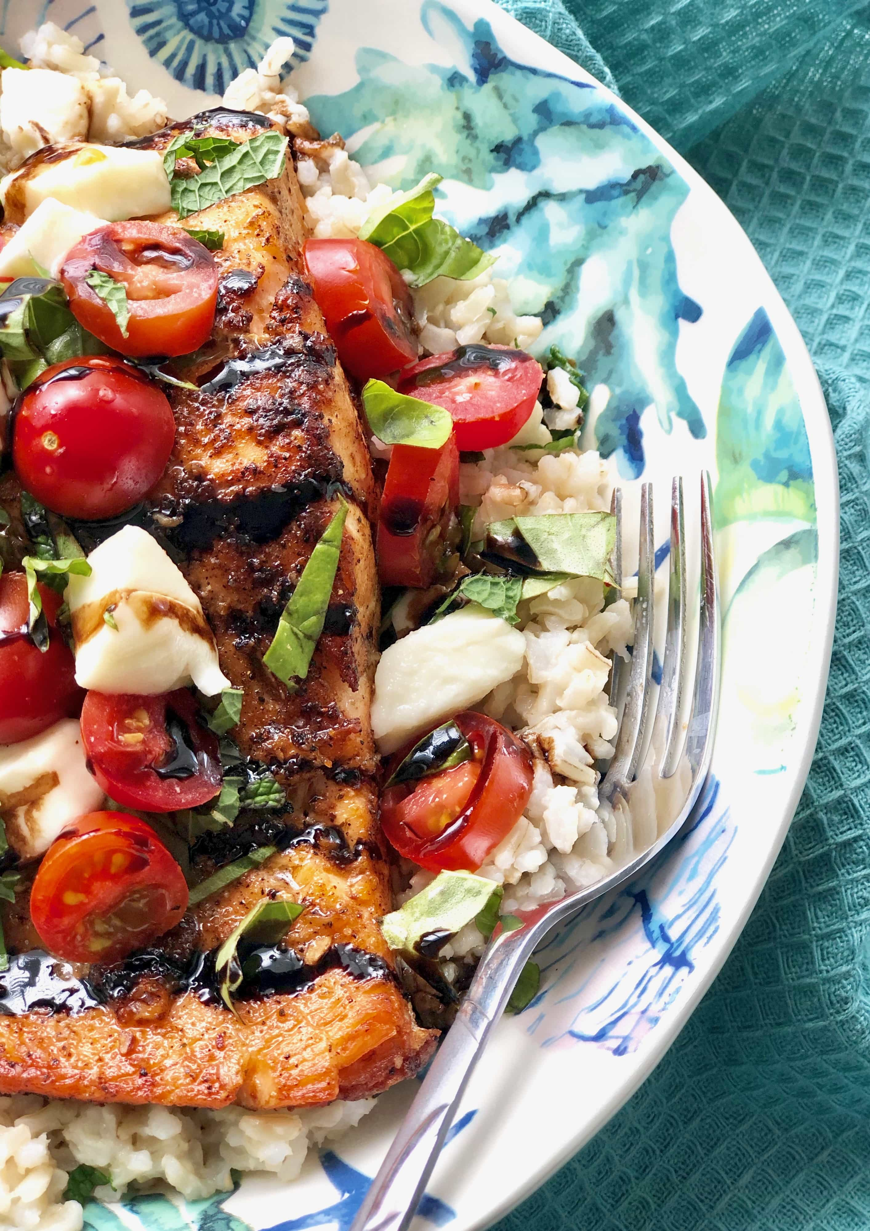 salmon with caprese salad on a pan