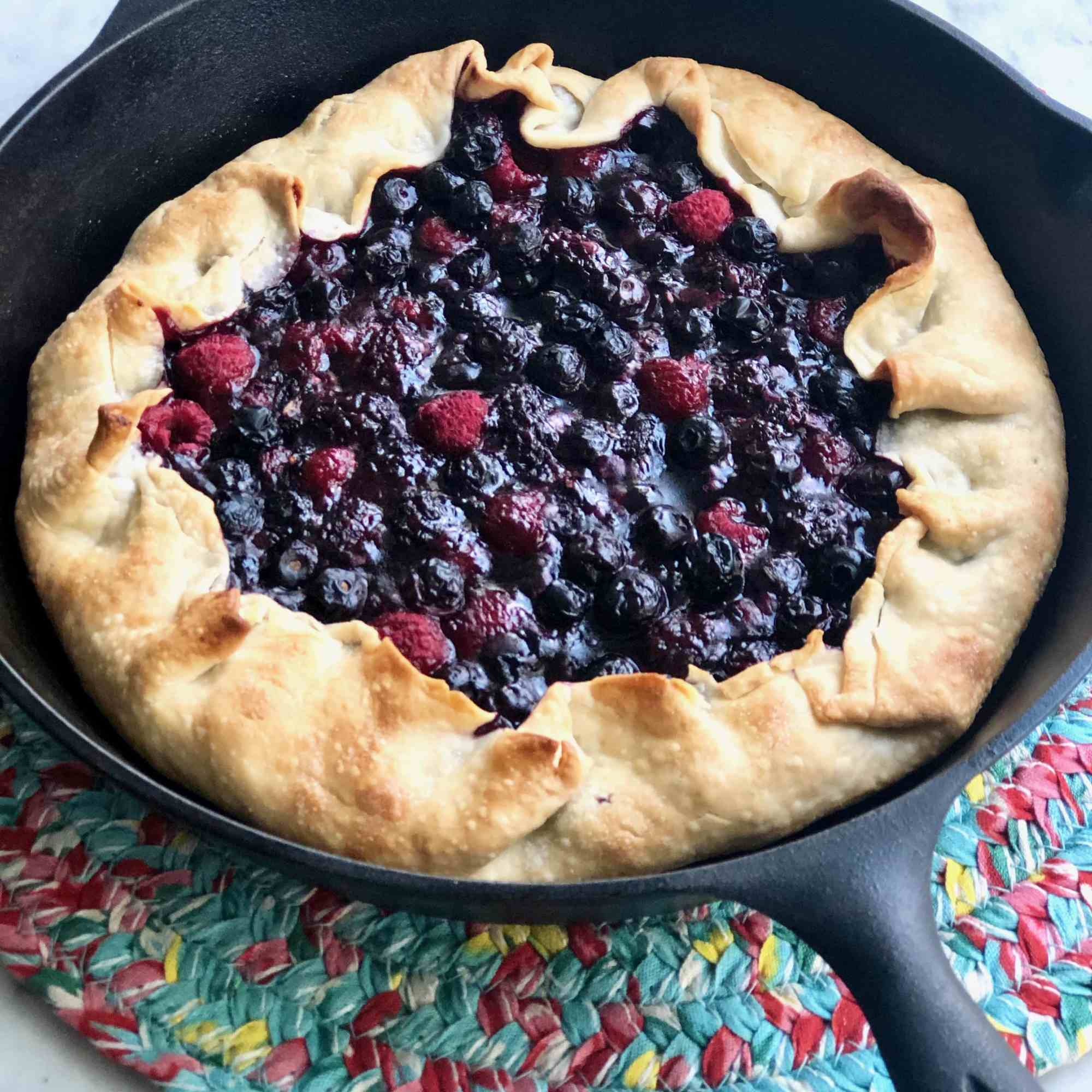 dough wrapped over berries in a cast iron skillet on a colorful placemat