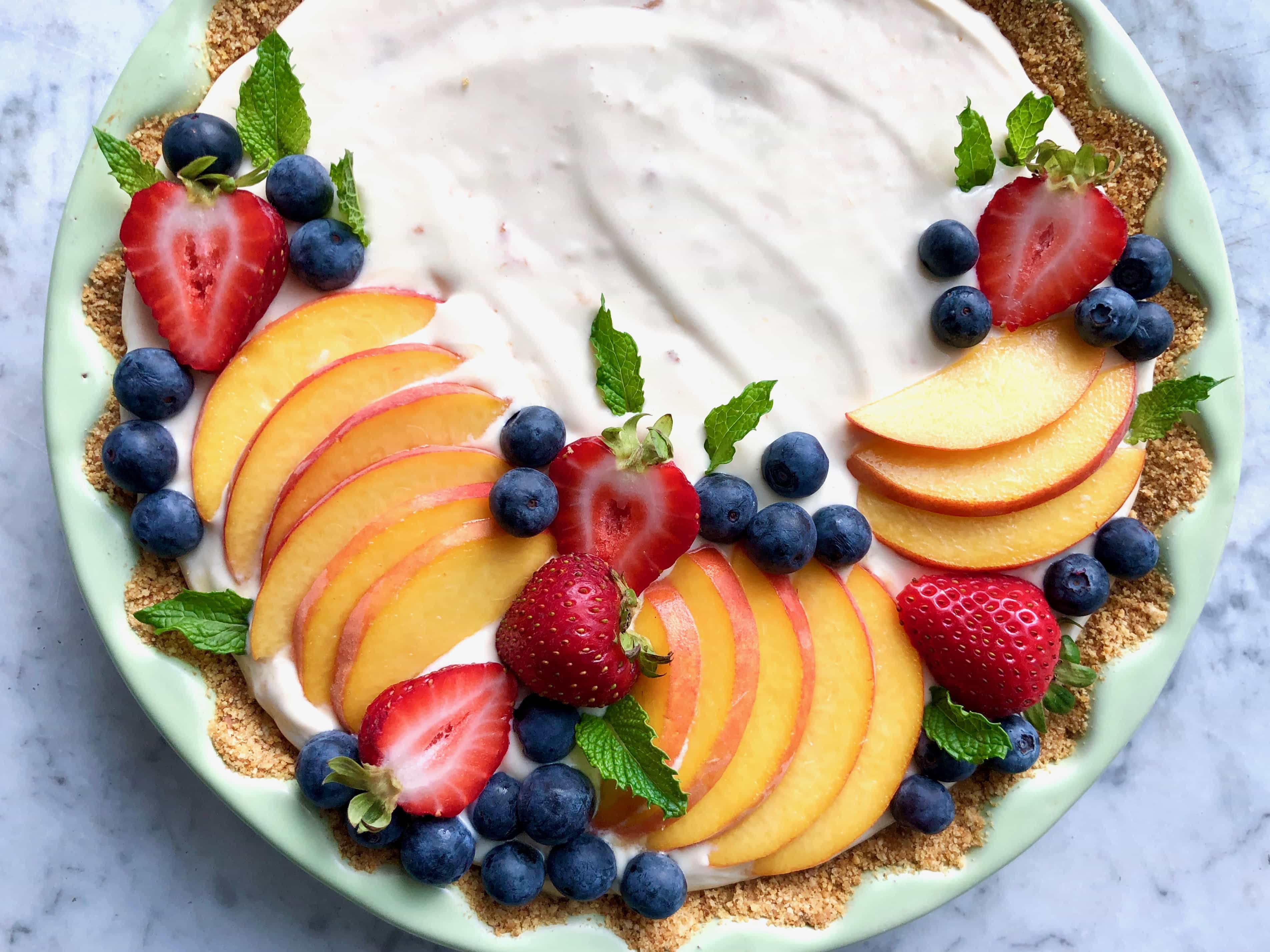tart garnished with berries in a green tart dish