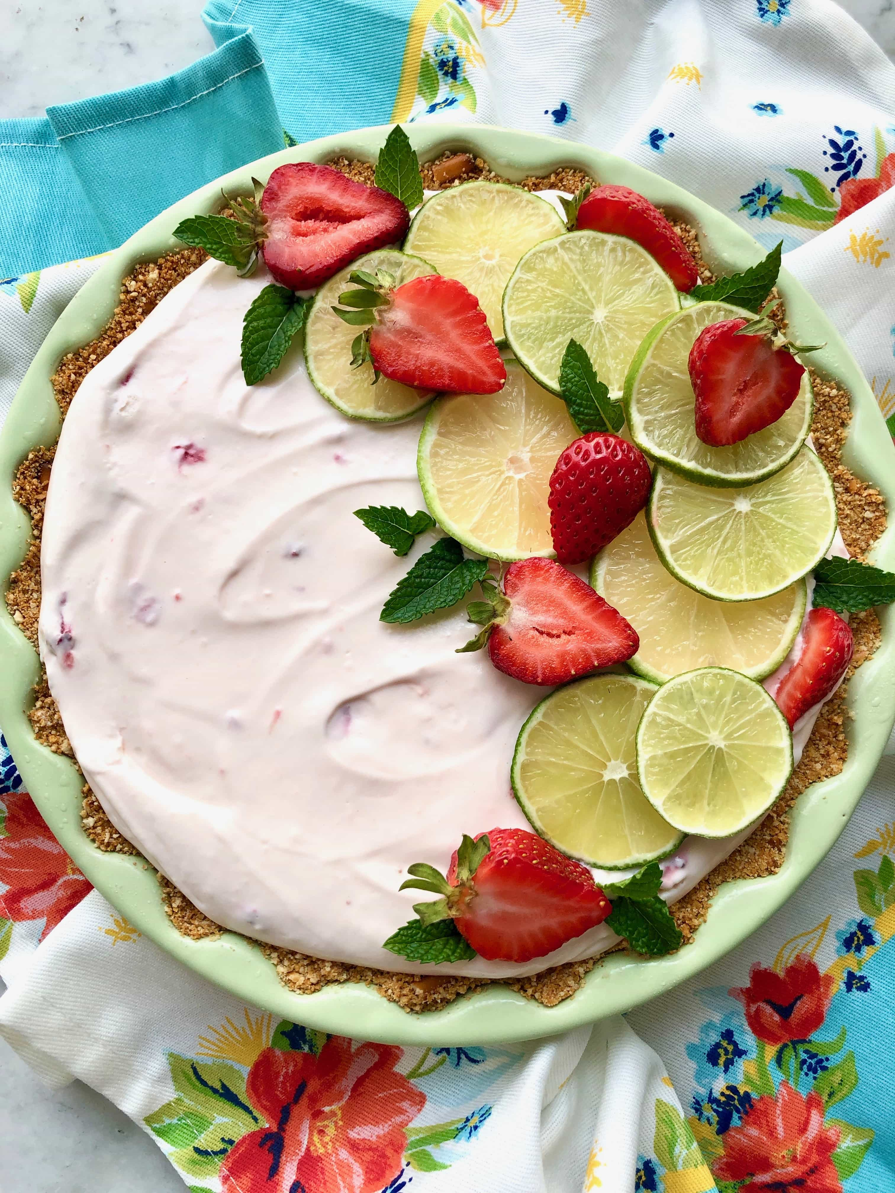 strawberry margarita pie in a green pie plate on a floral towel