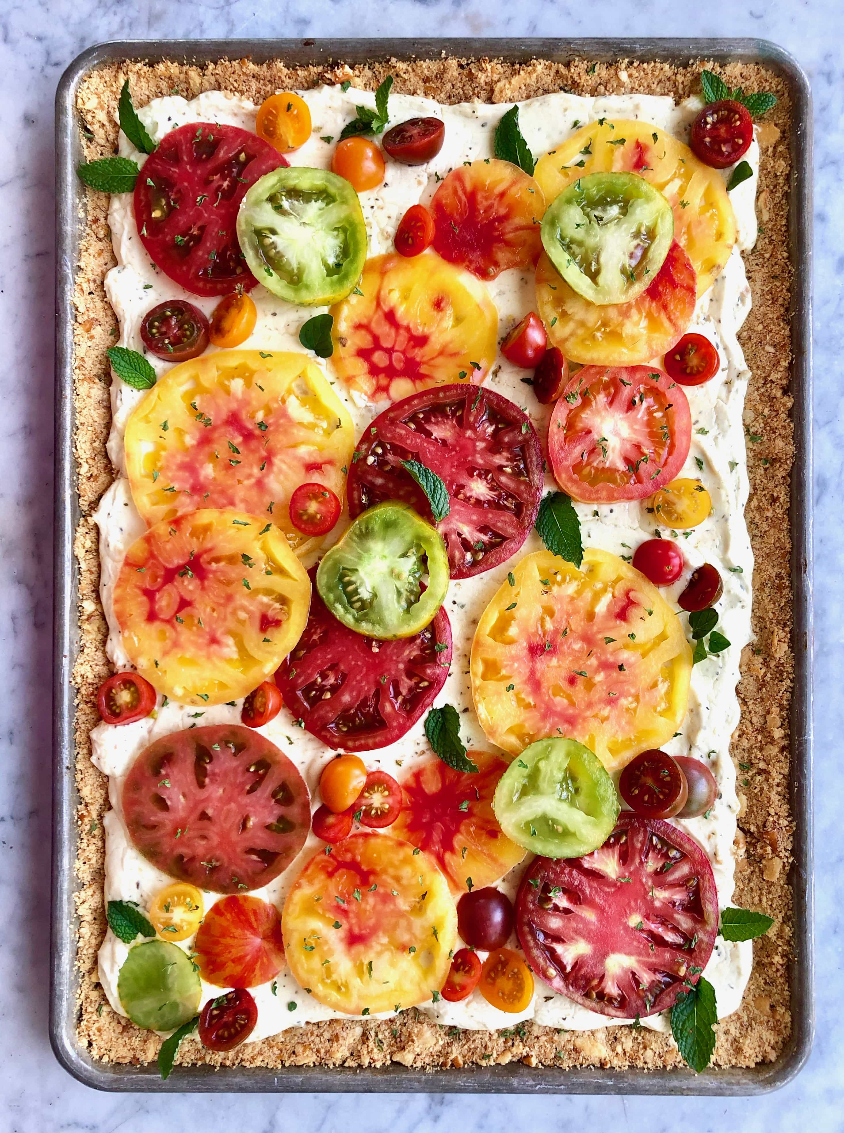 heirloom tart with colorful tomatoes on a sheet pan