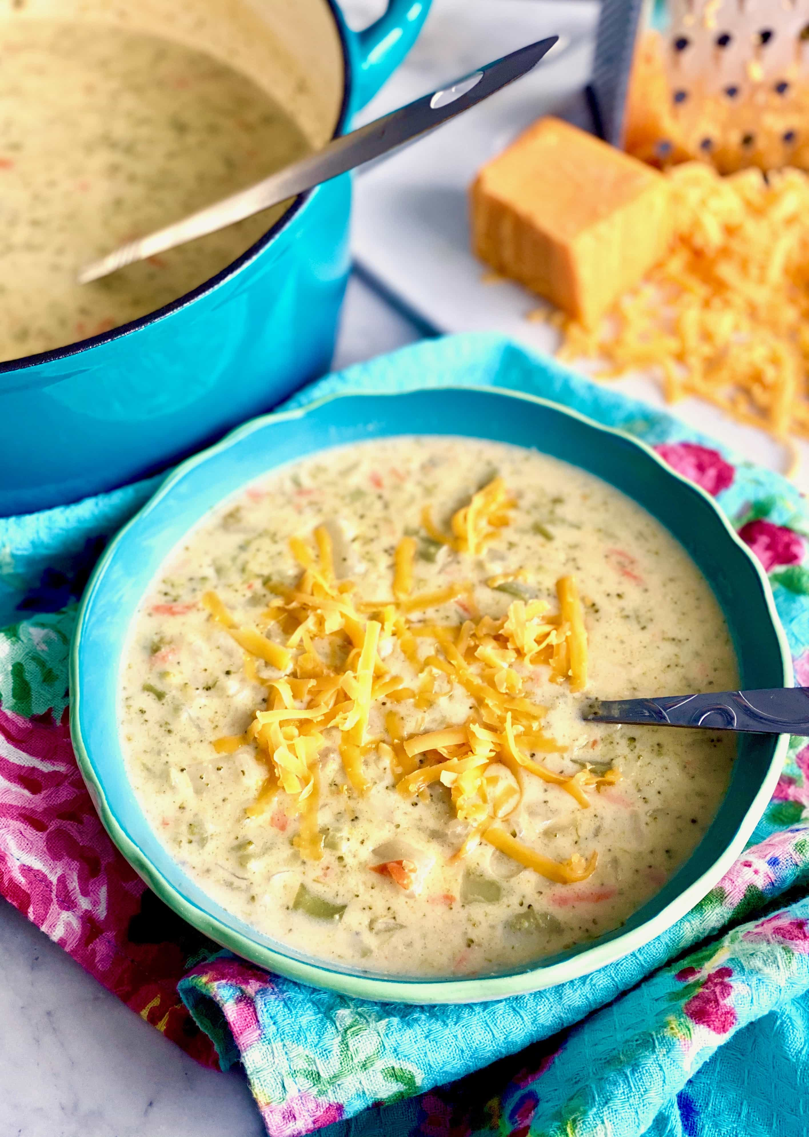 broccoli cheese chowder in blue bowl with dutch oven in background