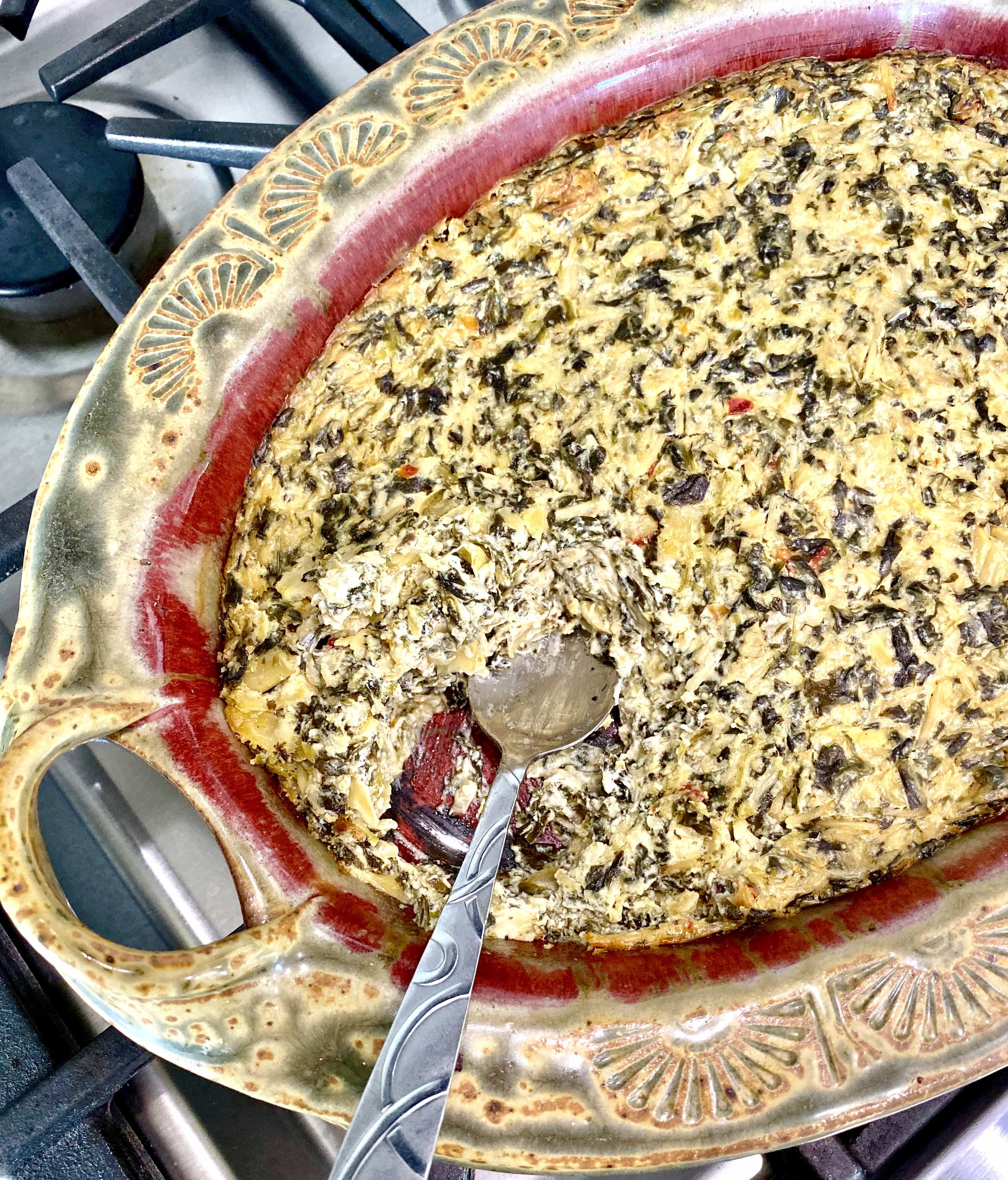 spinach artichoke dip in a red pottery dish