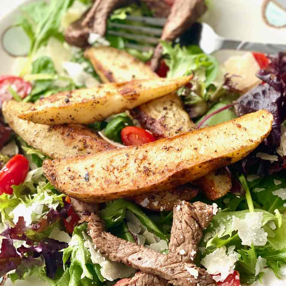 fried potatoes and steak on salad