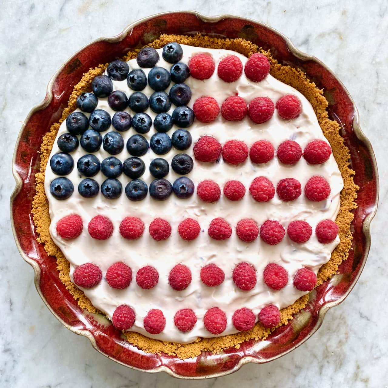 pie with flag decorations on top out of raspberries and blueberries