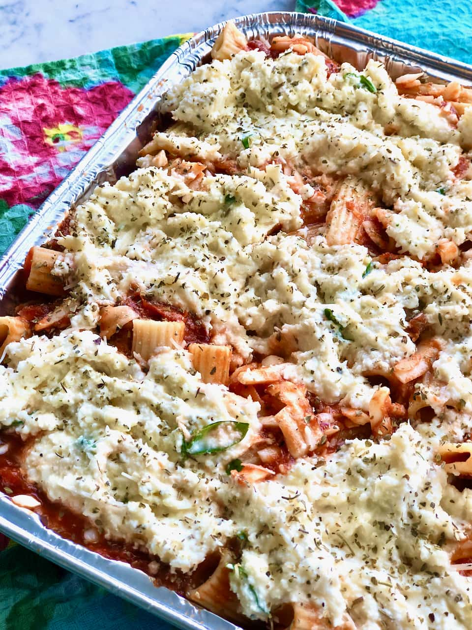 cheese topped ziti with tomato sauce in a to go pan