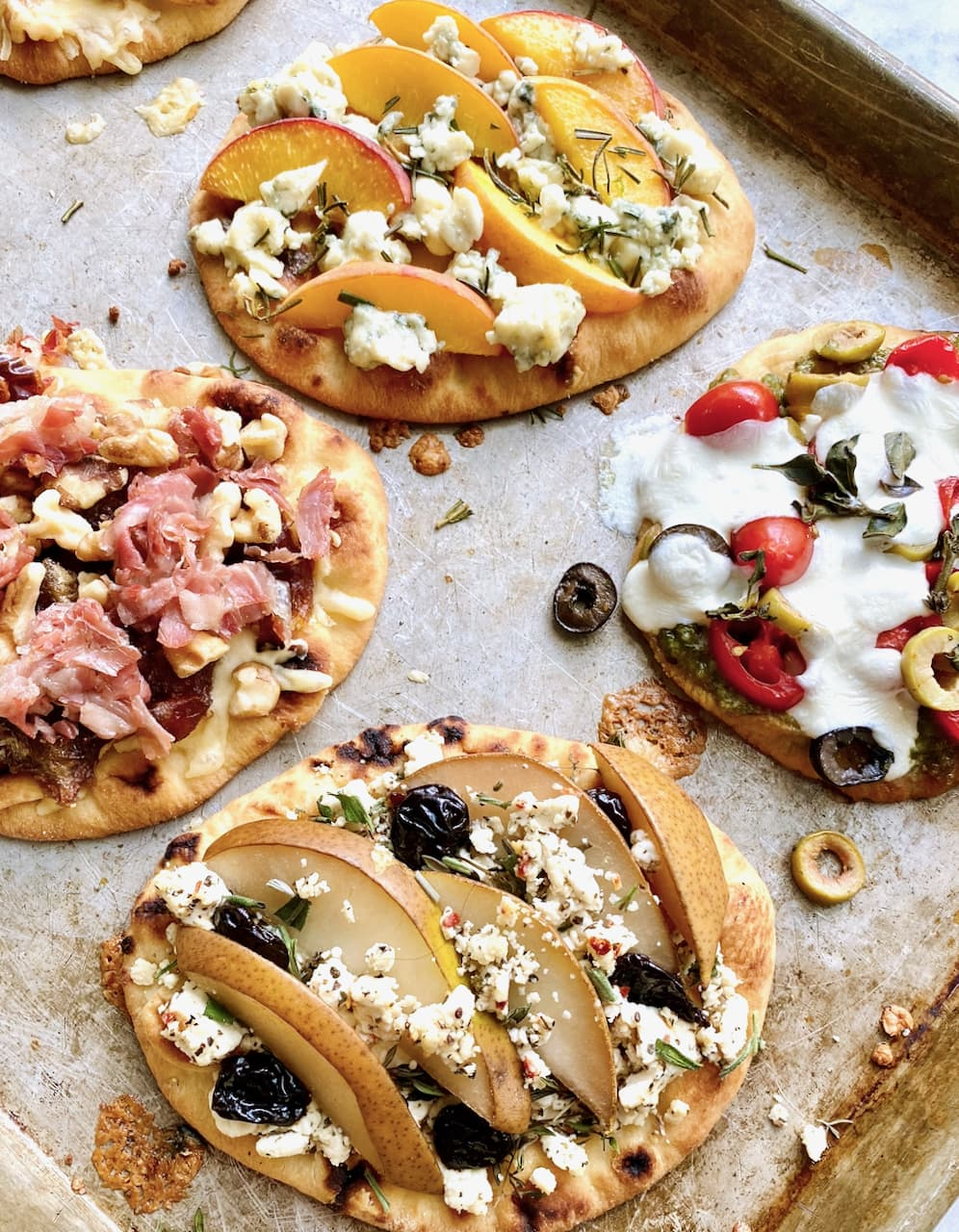 four flatbreads on a sheet pan showing how to build your own
