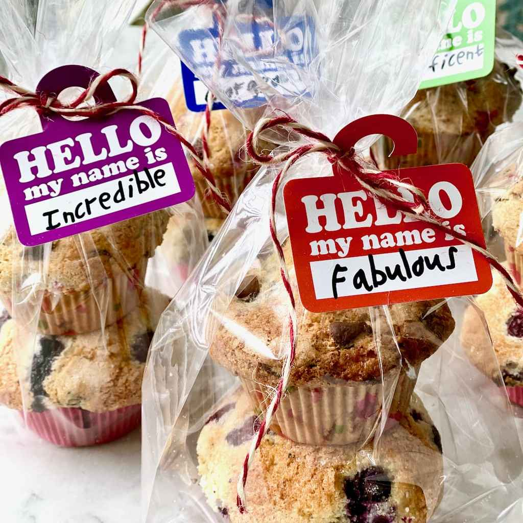 raspberry chocolate muffins wrapped in cellophane with hello my name is tags attached