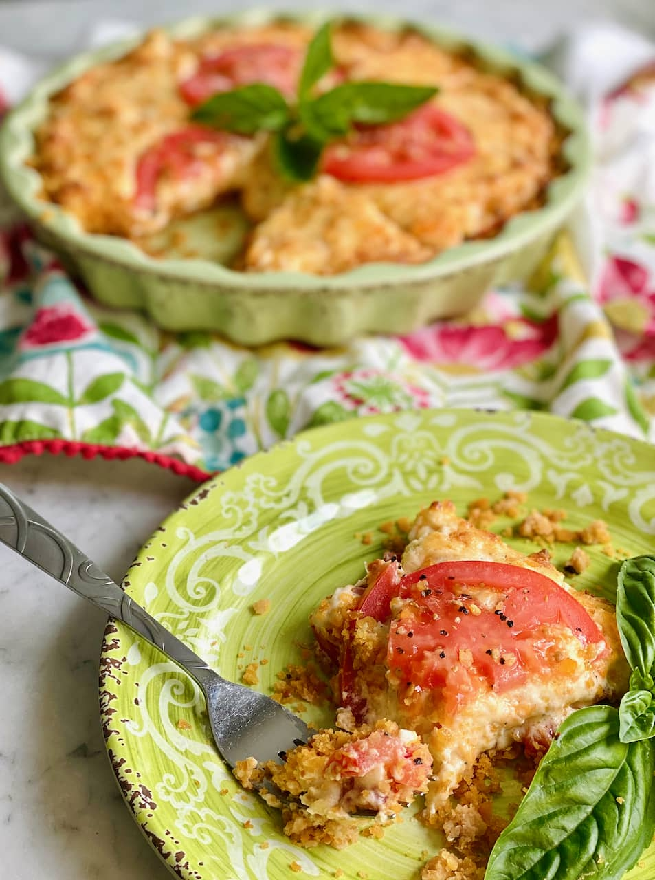 slice of tomato pie on a green dish with basil and an entire pie in the background