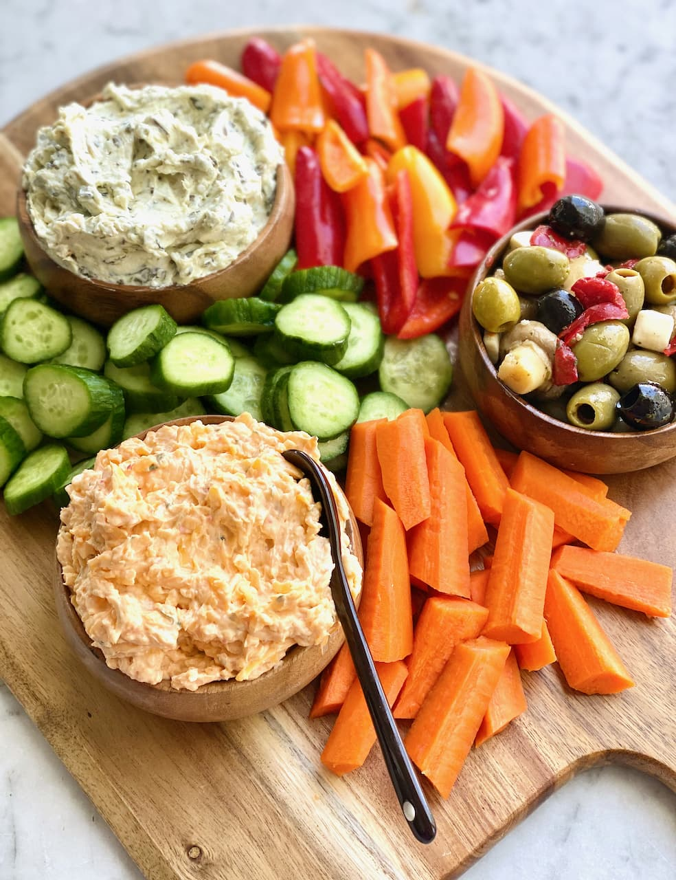 pimento cheese, spinach artichoke dip and antipasti surrounded by colorful veggies