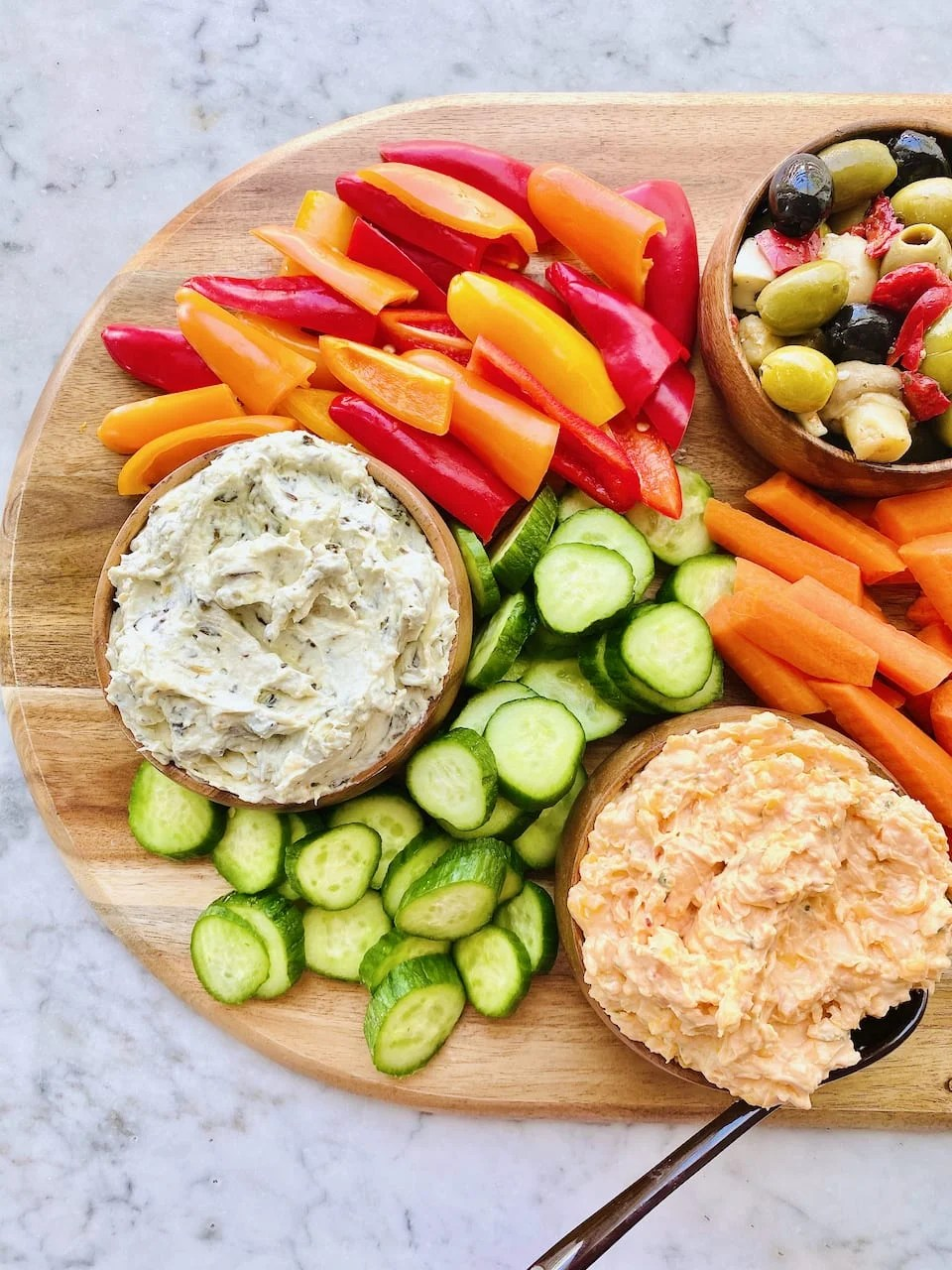 pizza wooden board with red and orange pepper, cucumbers, pimento cheese and veggies
