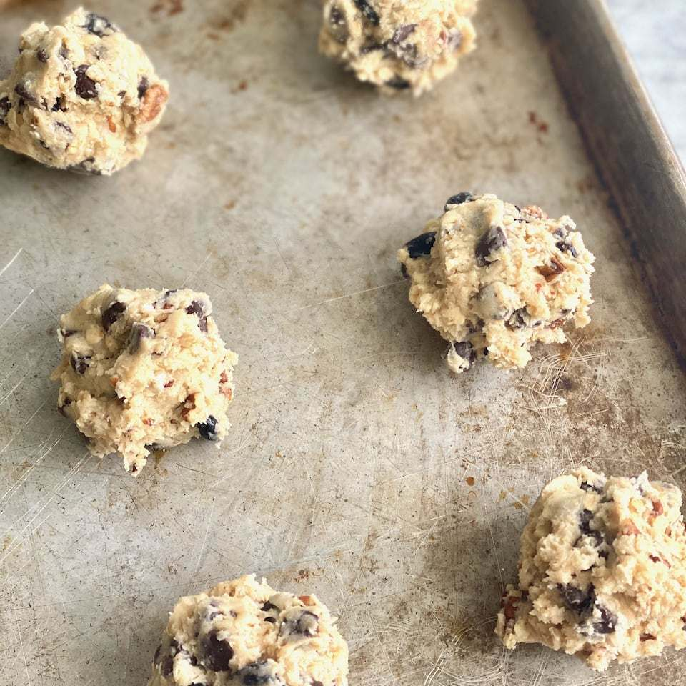 scoops of cookie dough on a sheet pan