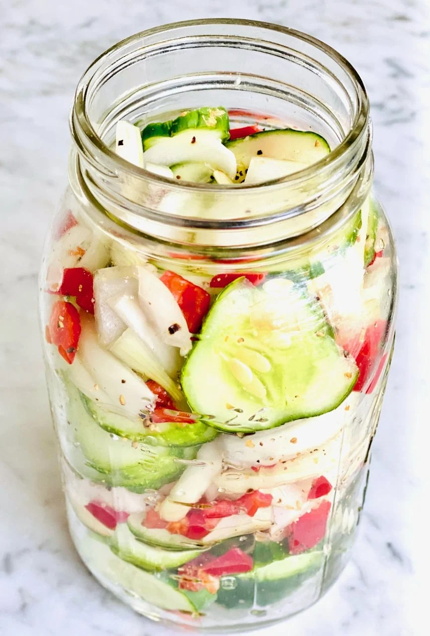 single jar of cucumbers, onions and red peppers on a white background