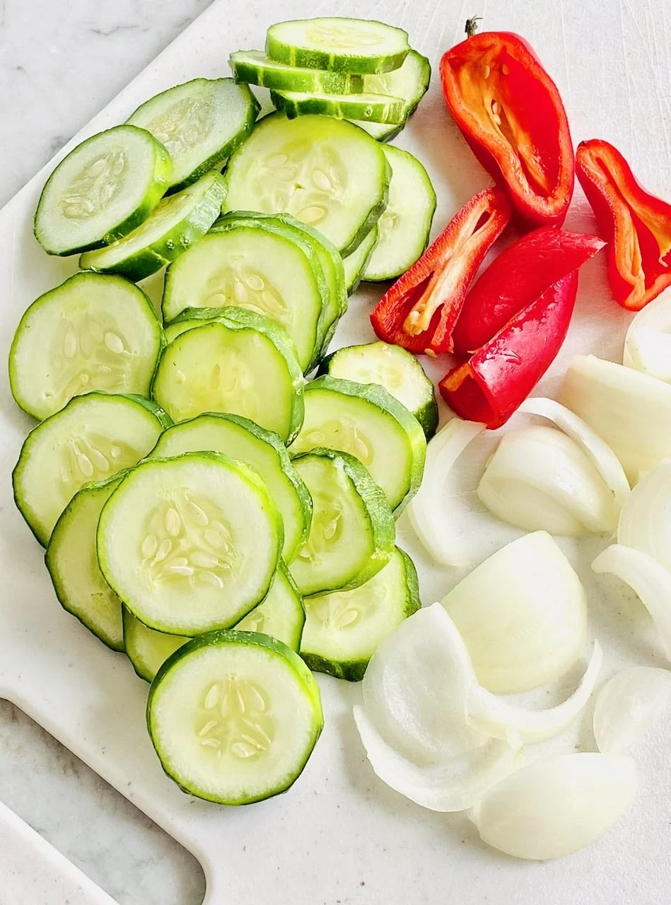 cucumbers, red pepper and onions cut on a cutting board