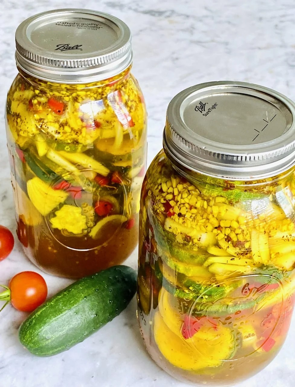 two jars of bread and butter pickles with lids and seals
