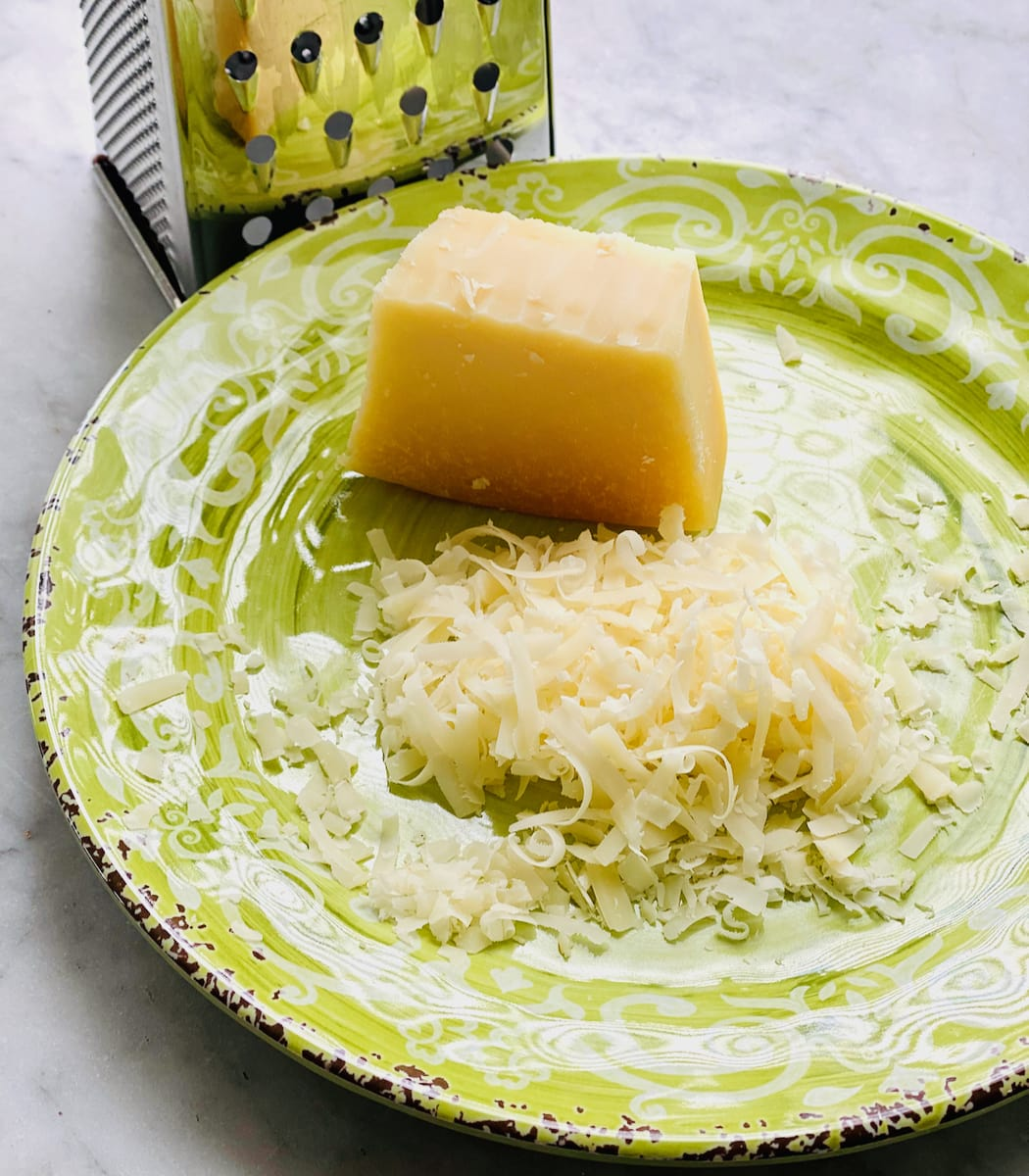 a wedge of parmesan cheese being grated onto a green plate