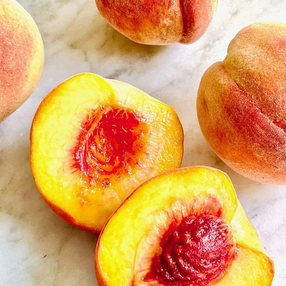 freestone peaches in halves and wholes showing the pit on a white background