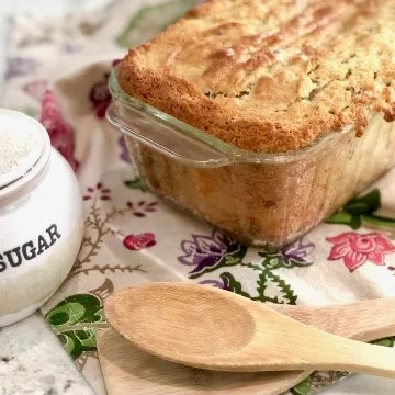 banana bread in a glass dish with sugar bowl and wooden spoons beside it